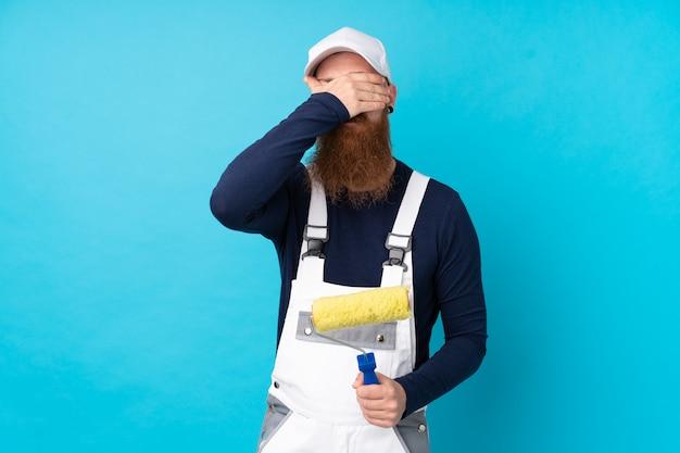 Maler mann mit langem bart über isolierten blauen wand, die augen durch hände bedeckt Premium Fotos