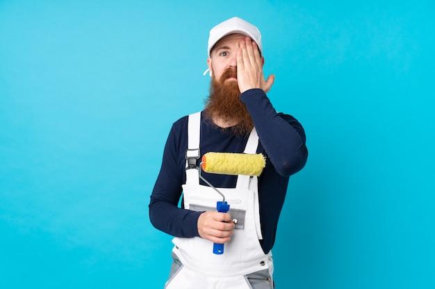 Maler mann mit langem bart über isolierter blauer wand, die ein auge von hand bedeckt Premium Fotos
