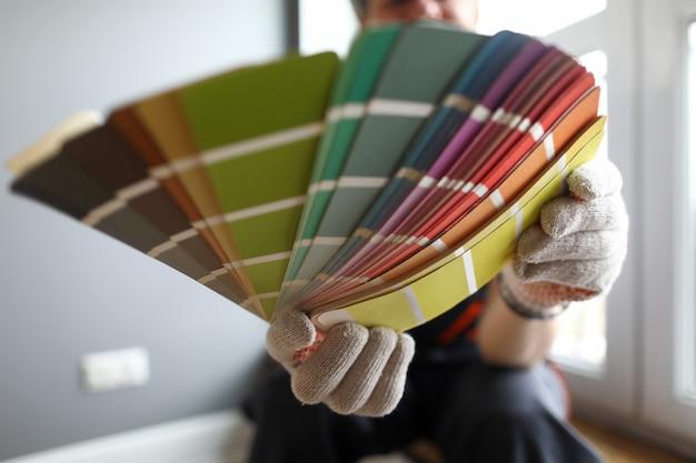 Maler zeigt farbmuster zur reparatur. der mensch wählt ein farbschema für die wände im haus Premium Fotos