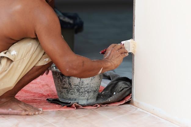 Maleranstrichwand mit pinsel und schwarzem farbeimer. architektur- und tiefbaukonzept Premium Fotos
