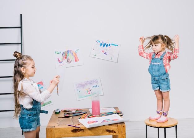 Malerei des kleinen mädchens, die mädchen auf stuhl aufwirft Kostenlose Fotos