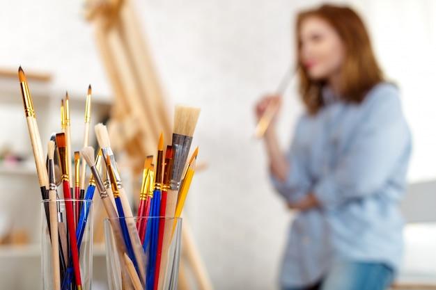 Malerei liefert pinsel und staffelei, arbeitsplatz des künstlers. Premium Fotos