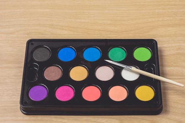 Malerpinsel- und aquarellpalette auf der braunen hölzernen tabelle unter verwendung für künste und bildung Premium Fotos