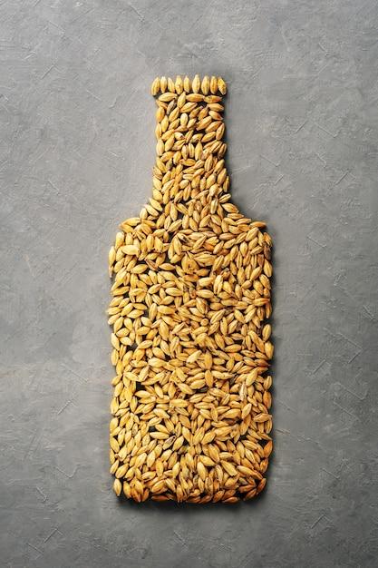 Malzkörner werden als bierflasche auf grauem betonhintergrund ausgelegt. Premium Fotos