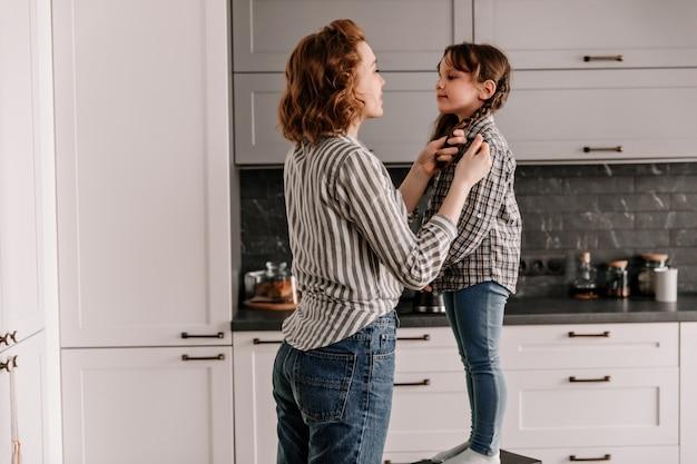 Mama befestigt vorsichtig die haare ihrer tochter, die auf einem stuhl steht. Kostenlose Fotos