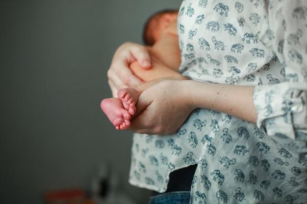 Mama behält das neugeborene. mutter stillt baby. mama umarmt das baby sanft Premium Fotos