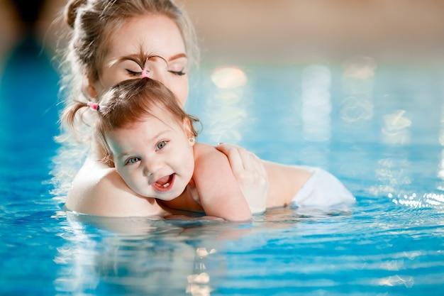 Mama und baby schwimmen im pool. Premium Fotos