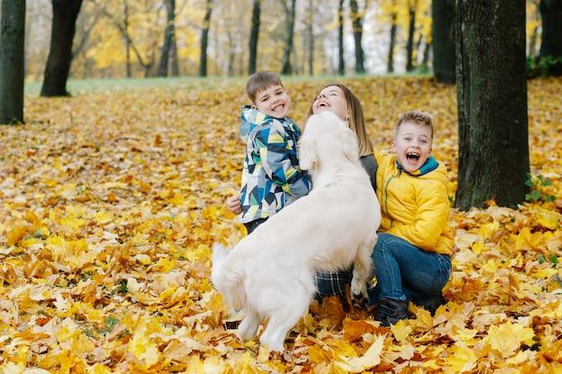 Mama und ihre söhne spielen im herbst mit einem hund im park Premium Fotos