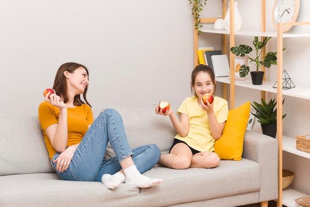 Mama und mädchen essen früchte Kostenlose Fotos