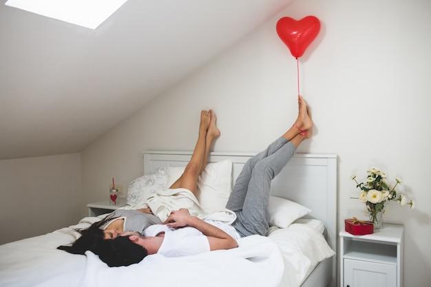 Man hält eine herzförmigen Ballon mit seinen Füßen | Download der ...
