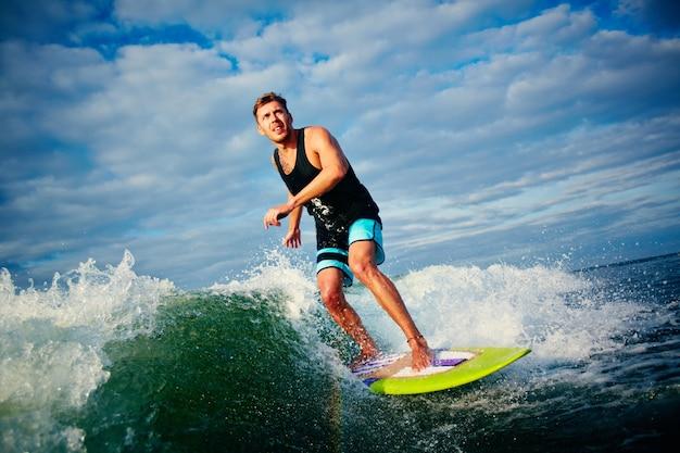 Man hat spaß mit dem surfbrett Kostenlose Fotos