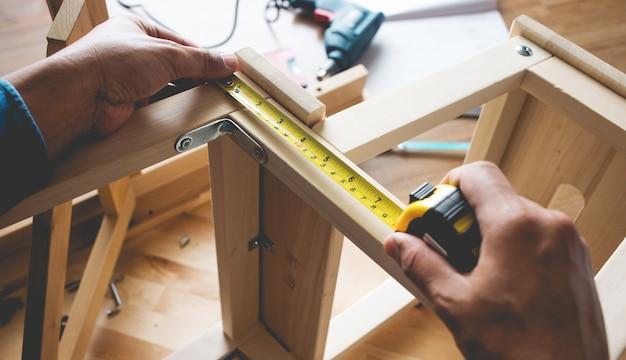 Man montiert holzmöbel, repariert oder repariert das haus mit gelben maßbändern. Premium Fotos
