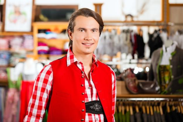 Man probiert tracht oder lederhosen in einem geschäft aus Premium Fotos