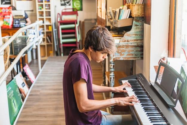 Man sitzt und spielt synthesizer Kostenlose Fotos