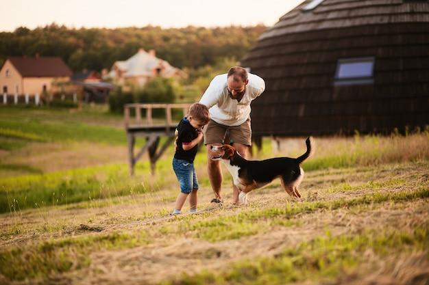 Man spielt mit seinem sohn und einem hund auf dem feld Kostenlose Fotos