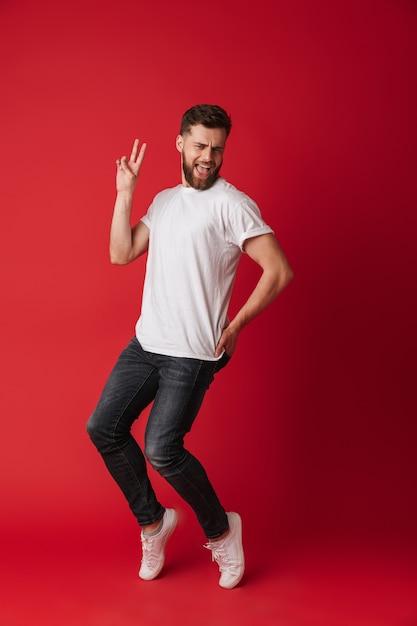 Man tanzt lokalisiert über rotem wandhintergrund. Premium Fotos