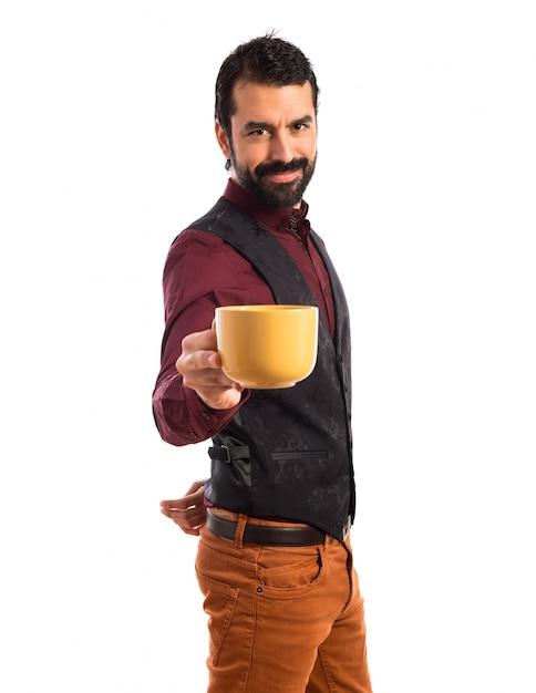 Man trägt eine weste mit einer tasse kaffee Kostenlose Fotos