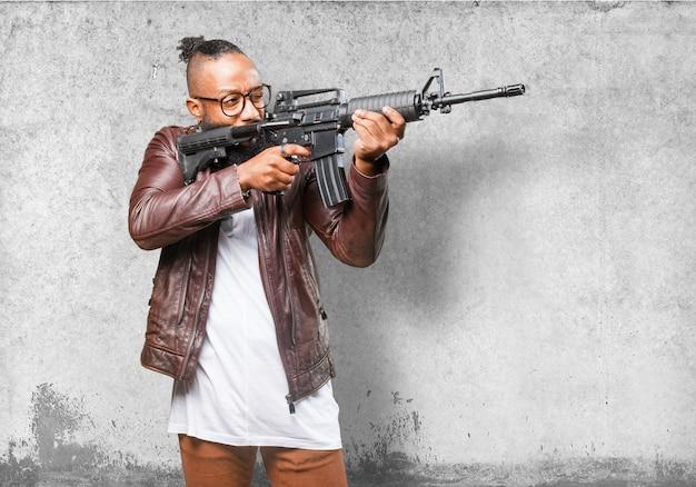 Man zeigt mit einer maschinenpistole Kostenlose Fotos