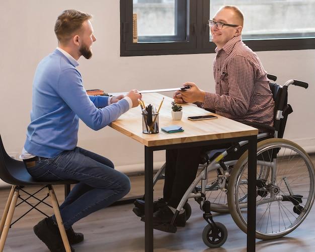 Manager arbeitet mit behinderten arbeitnehmern zusammen Kostenlose Fotos