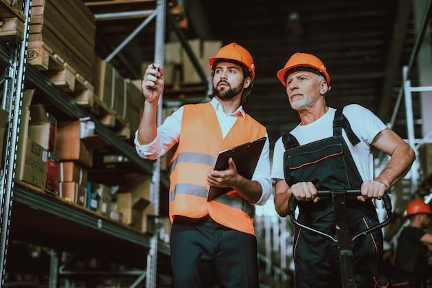 Manager im hardhat, der mit lagerarbeiter spricht Premium Fotos