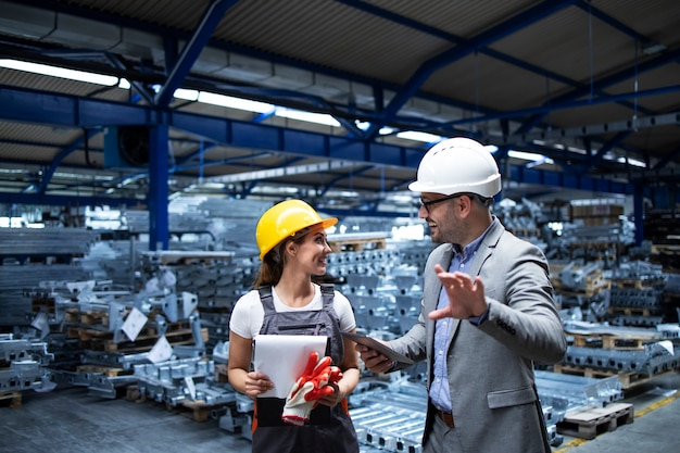Manager mit helm und industriearbeiter diskutieren über die produktion in der metallfabrik Kostenlose Fotos