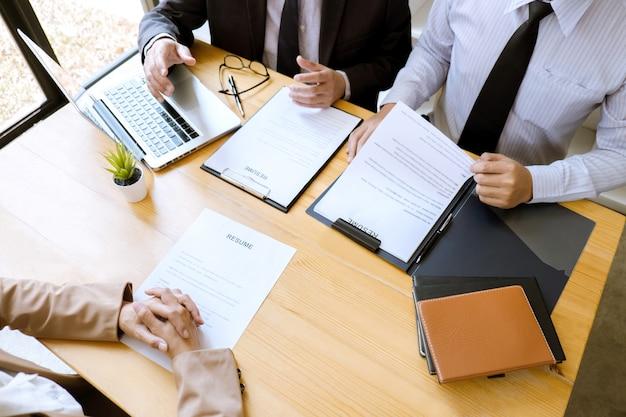 Manager mit zwei auswahlausschüssen, der einen lebenslauf während eines vorstellungsgesprächs für das einstellungsgespräch liest Premium Fotos