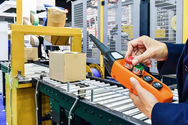 Manager überprüfen und steuern automatisierungspappschachteln auf förderband im lagerhaus. Premium Fotos