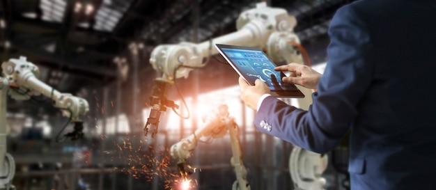 Manager-wirtschaftsingenieur, der tablettenkontroll- und -steuerungsautomatisierungsrobotermaschine verwendet Premium Fotos