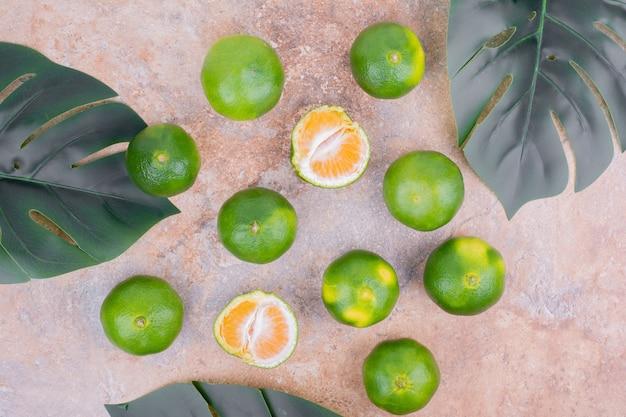 Mandarinen auf einer oberfläche mit grünen blättern Kostenlose Fotos