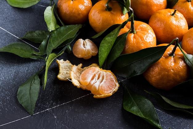 Mandarinen mit grünen blättern schließen oben auf dunkelheit Kostenlose Fotos