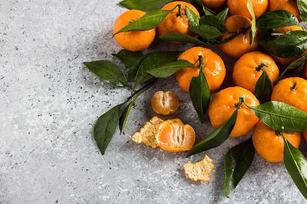 Mandarinen mit grünen blättern schließen oben auf licht Kostenlose Fotos