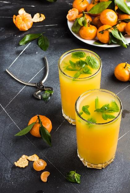 Mandarinesaft in gläsern auf dunkel Kostenlose Fotos