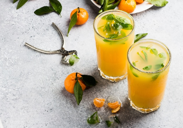 Mandarinesaft in gläsern auf licht Kostenlose Fotos