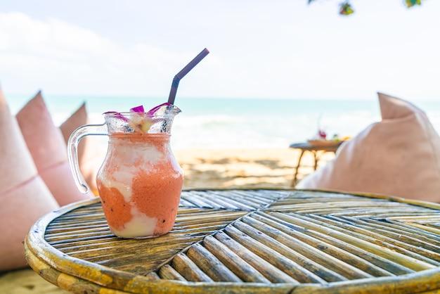 Mango, ananas, wassermelone und joghurt oder joghurt smoothies glas mit meeresstrand Premium Fotos