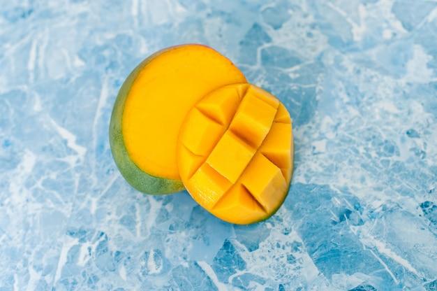 Mango auf blauem hintergrund. methoden zum schneiden von exotischen früchten Premium Fotos