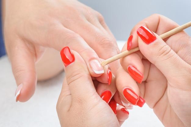 Maniküre auftragen - nagelhaut reinigen Premium Fotos