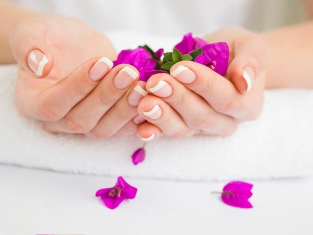 Manikürte frauenhände, die bunte blumen halten Premium Fotos