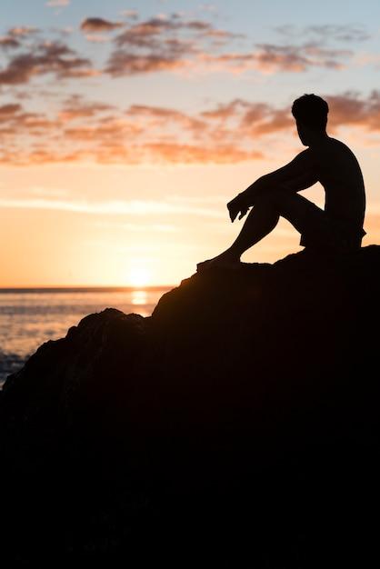 Mann am strand bei sonnenuntergang entspannen Kostenlose Fotos