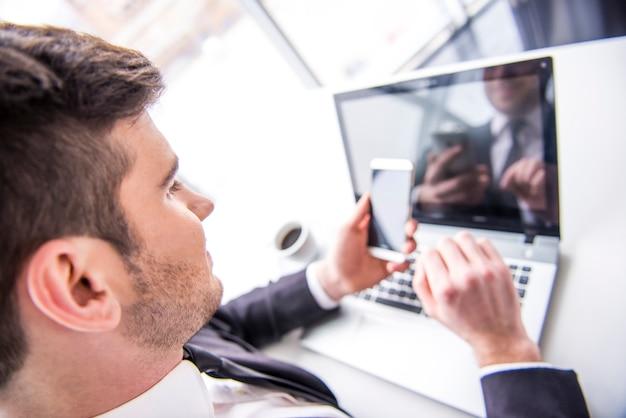 Mann arbeitet mit laptop und hält einen handy. Premium Fotos