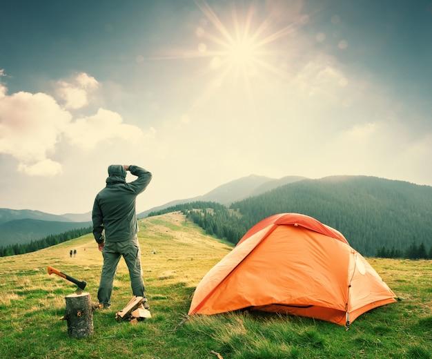 Mann auf berg nahe orange zelt schaut in die ferne Premium Fotos