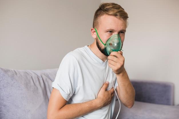Mann auf couch mit asthmavernebler Kostenlose Fotos