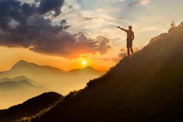 Mann auf dem gipfel des berges. emotionale szene. junger mann mit dem rucksack, der mit den angehobenen händen auf einen berg steht. Premium Fotos