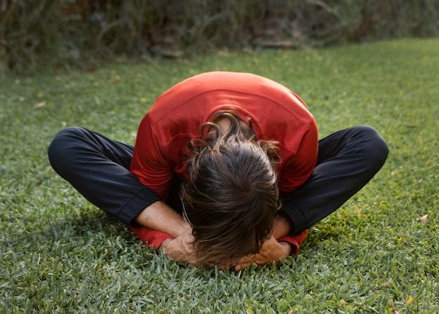 Mann auf dem rasen im freien, der yoga tut Premium Fotos