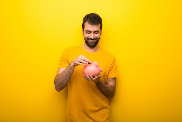 Mann auf der lokalisierten vibrierenden gelben farbe, die ein sparschwein nimmt und glücklich ist, weil es voll ist Premium Fotos