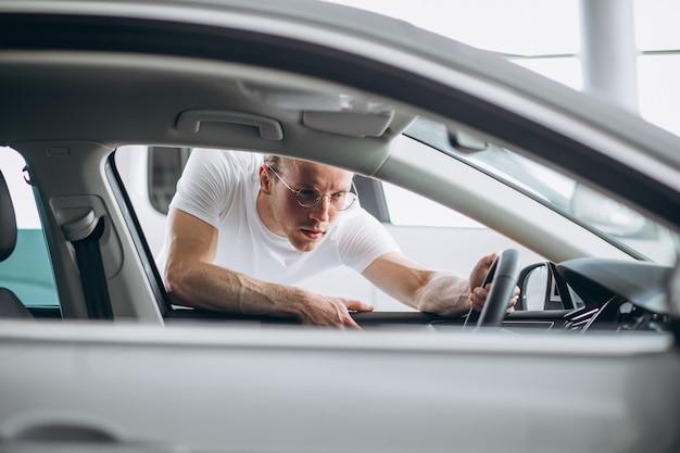 Mann auf der suche nach einem auto in einem autosalon Kostenlose Fotos