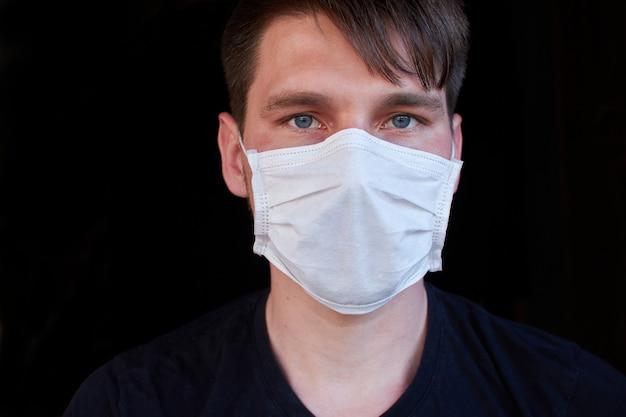 Mann auf dunkler wand in einer medizinischen maske. schutz vor viren, bakterien und krankheiten Premium Fotos