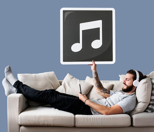 Mann auf einer couch, die eine ikone der musikalischen anmerkung hält Kostenlose Fotos