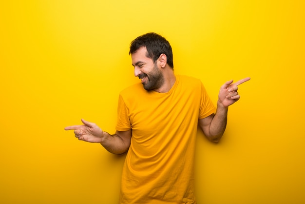 Mann auf lokalisierter vibrierender gelber farbe genießen zu tanzen, während sie musik an einer party hören Premium Fotos