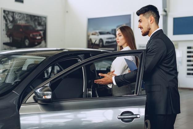 Mann autohändler zeigt einer frau käufer ein neues auto Premium Fotos