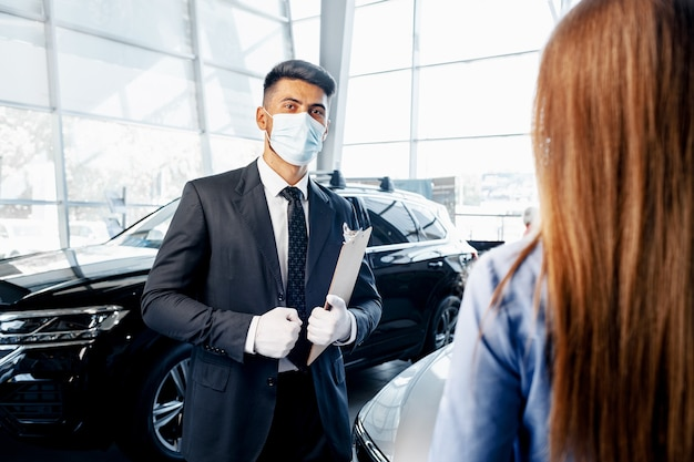 Mann-autoverkäufer in der gesichtsmaske, die mit einem kunden im ausstellungsraum spricht Premium Fotos